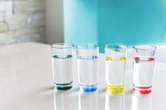 Woda w przejrzystych szkłach z barwionym dnem na stole w pokoju fotografia royalty free