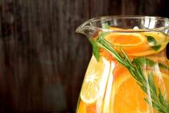 Woda z pomarańcze, cytryny i mandarynki plasterkami w szklanym dzbanku, zdjęcia stock