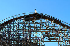 Wodan wooden coaster top head. Top head of the wooden roller coaster Wodan with its sign in Europa Park Rust, Germany, set against a blue sky Royalty Free Stock Photo