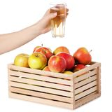 A wodden box of apples a glass of apple juice in hand. On a white background Isolation Royalty Free Stock Photo