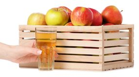 A wodden box of apples a glass of apple juice in hand. On a white background Isolation Stock Photos