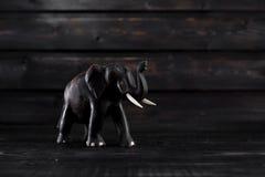 Wodden-Elefantstatue auf hölzernem Hintergrund Stockbild