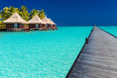 Wodden jetty extended into azure water of lagoon with villas ove Stock Images