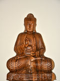 Wodden sitting buddha. Wodden colored sitting buddha and withe Backround royalty free stock image