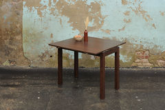 Woden table with vase and wallnuts near old plastered wall Royalty Free Stock Images