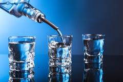 Wodka, der aus der Flasche in Glas in einer Stange gießt stockfotografie
