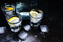 wodka Schoten, glazen met wodka en citroen met ijs Donkere steenachtergrond royalty-vrije stock fotografie