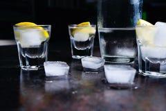 wodka Schoten, glazen met wodka en citroen met ijs Donkere steenachtergrond stock foto