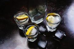 wodka Schoten, glazen met wodka en citroen met ijs Donkere steenachtergrond stock fotografie