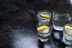wodka Schoten, glazen met wodka en citroen met ijs Donkere steenachtergrond stock afbeelding