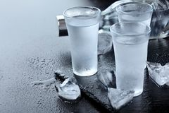 wodka Schoten, glazen met wodka met ijs Donkere steenachtergrond De ruimte van het exemplaar Selectieve nadruk stock afbeelding