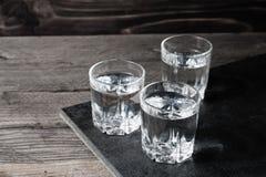 Wodkaschoten met ijsblokjes op zwarte steen, royalty-vrije stock afbeelding