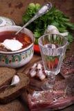 Wodkaweinglas, Borschtsch mit Sauerrahm und salziges Fett stockfoto