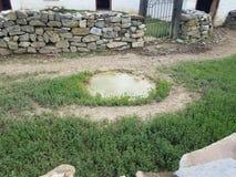 Wodna kałuża w kamiennej ścianie i ziemi obrazy royalty free