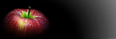 Wodna kropelka na glansowanej powierzchni czerwony jabłko na czarnym tle obraz stock