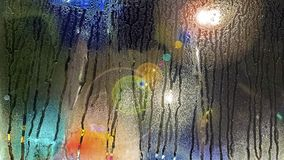 Wodna kropelka na wiatrowej osłonie w miasto ruchu drogowym z wieloskładnikowym colour plamy tłem i woda ruch przez kropelek zdjęcie royalty free