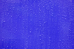 Wodna kropla na zmroku - błękitny tło Zdjęcie Stock