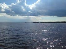 Wodna powierzchnia pod chmurnym niebem Obrazy Royalty Free