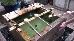 Wodne ablucje kobiet ręki dla puryfikacja obrządku w Nishiki Tenmangu świątyni, Kyoto, Japonia zbiory