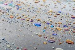 Wodne kropelki i produkt przerobu ropy naftowej na zmrok powierzchni, barwioni punkty na powierzchni obrazy stock