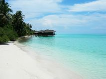 Wodni bungalowy nad turkusowego błękita oceanem z bielem wyrzucać na brzeg w Maldives obraz stock