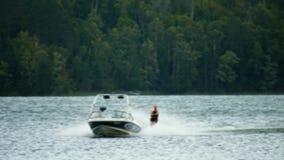 Wodniactwo w Minnestoa Wodna narciarka ciągnął prędkości motorową łodzią na pięknym jeziorze zbiory
