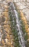 Wodny bieg puszek kamienna ściana Obrazy Stock