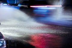 Wodny chełbotanie od samochodowych kół jedzie przy nocą podczas burzowego w fotografia stock