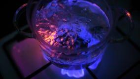 Wodny gotowanie w szklanym garnku przy benzynową kuchenką zbiory wideo