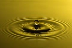 Wodny kropli zakończenie up z koncentrycznych czochr colourful żółtym sura zdjęcia stock