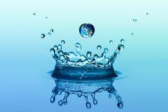 Wodny pluśnięcie w korona kształcie i spada kropli z ziemskim wizerunkiem obrazy royalty free