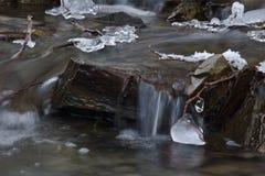 Wodny spływanie nad skałą w małym strumieniu z kawałkami lód tęsk ujawnienie obrazy royalty free