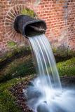 Wodny spadać kaskadą od kanalizacja metalu drymby wspinał się w ściana z cegieł Fotografia Royalty Free