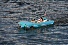 Wodny taxi, Błękitny rocznika samochód, Śmieszni ludzie fotografia royalty free