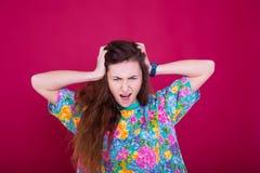 Woede en woedeconcept De jonge expressieve vrouw toont haar slecht gezicht Boos zenuwachtig geërgerd meisjesportret op rode achte Stock Fotografie