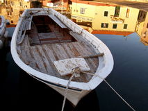Woeden boat on calm water. Wooden boat on calm water with reflection of surroundings on surface Stock Photography