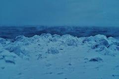 woedende overzees tijdens een sterk de winteronweer met ijs behandelde kust royalty-vrije stock fotografie