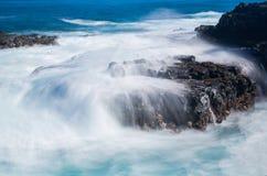 Woedende overzeese stromen over laverotsen op kustlijn stock afbeelding