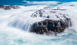 Woedende overzeese stromen over laverotsen op kustlijn royalty-vrije stock afbeelding