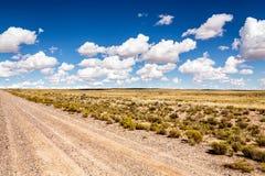 Woestenij, eenzaamheidslandweg in de woestijn met wolken Stock Fotografie