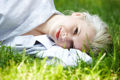 Wohl. Glückliche lächelnde Frau hat Rest auf Gras Stockfoto