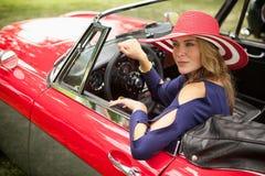 Wohlhabende Dame, die heraus ihr klassisches rotes europäisches Sportauto schaut Stockbild