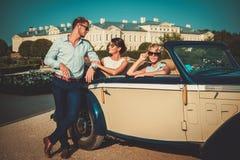 Wohlhabende Freunde nähern sich klassischem Kabriolett lizenzfreie stockfotos