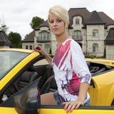 Wohlhabende junge Frau, die in ein Auto kommt Stockbild