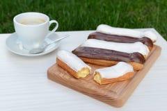 Wohlriechende Eclairs mit einer Schale starkem Kaffee Lizenzfreies Stockbild