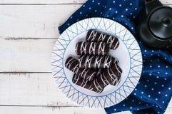 Wohlriechende Plätzchen des Chouxgebäcks in der dunklen Schokolade bedeckt mit weißer Dekoration auf einer weißen Platte auf eine Stockfoto
