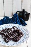 Wohlriechende Plätzchen des Chouxgebäcks in der dunklen Schokolade bedeckt mit weißer Dekoration auf einer weißen Platte auf eine Stockbild
