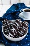 Wohlriechende Plätzchen des Chouxgebäcks in der dunklen Schokolade bedeckt mit weißer Dekoration und Schale coffe auf blauer Serv Lizenzfreie Stockfotografie