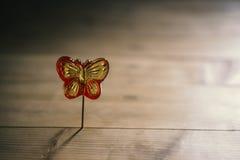 Wohlriechender Lutscher in Form eines Schmetterlinges auf einem Stock, Lichteffekte Stockfotos