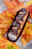 Wohlriechender Nachtisch auf Herbstlaub Eclairs im Herbst Delici lizenzfreie stockfotos